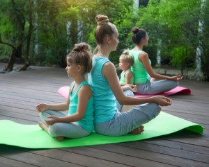 Mothers and daughters doing exercise practicing yoga outdoors